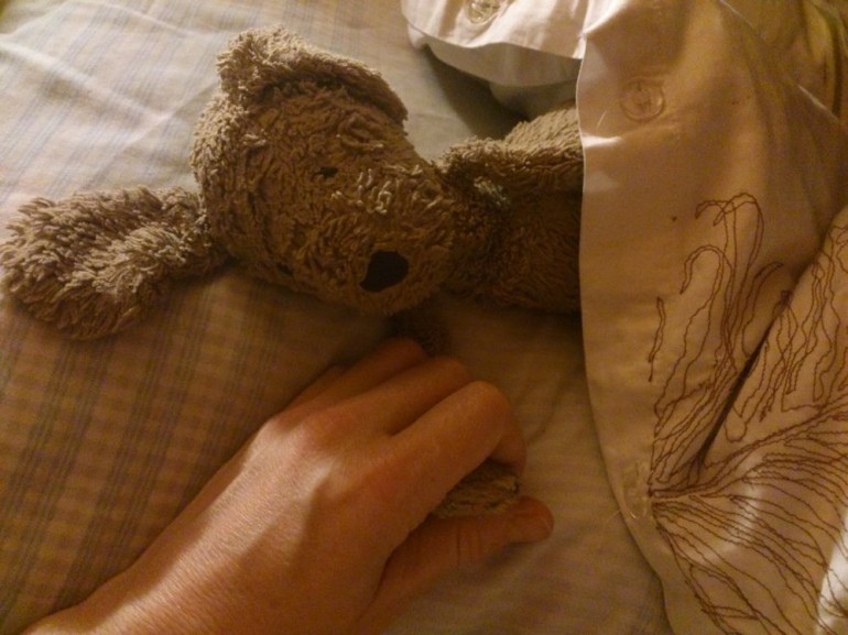 Comfort toy asleep in bed holding my hand, October 2013, Helen Sargeant ©
